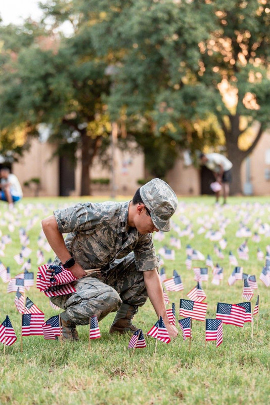 Cadet placing memorial flags on the UC lawn.