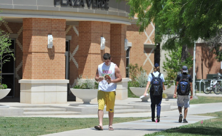 Student walking by Plaza Verde.