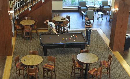 Student playing pool in the resident hall.
