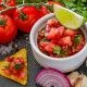 Salsa sauce and ingredients - tomates, onion, chili, garlic, lime, parsley, dark stone background, closeup