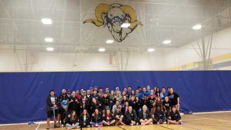 UREC student staff pictured in front of Dominic graphic on the gym curtain.