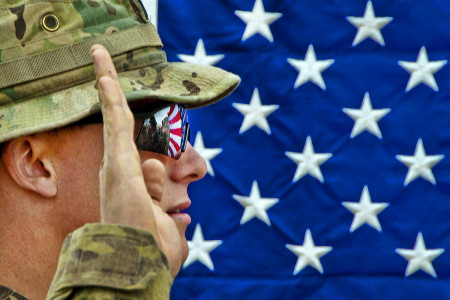 The American flag reflects in the glasses of an officer with the 82nd Airborne Division's  1st Brigade Combat Team as he reenlists another paratrooper on Combat Outpost Qara Baugh, Ghazni province, Afghanistan, April 22, 2012. (U.S. Army photo by Sgt. Reed Knutson)