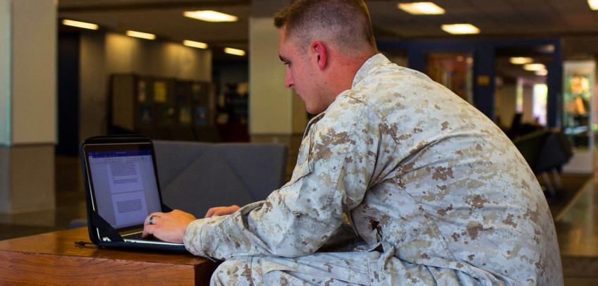 ASU student in Military uniform using a laptop.