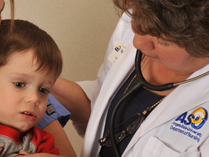 Nursing instructor and student examine a child.
