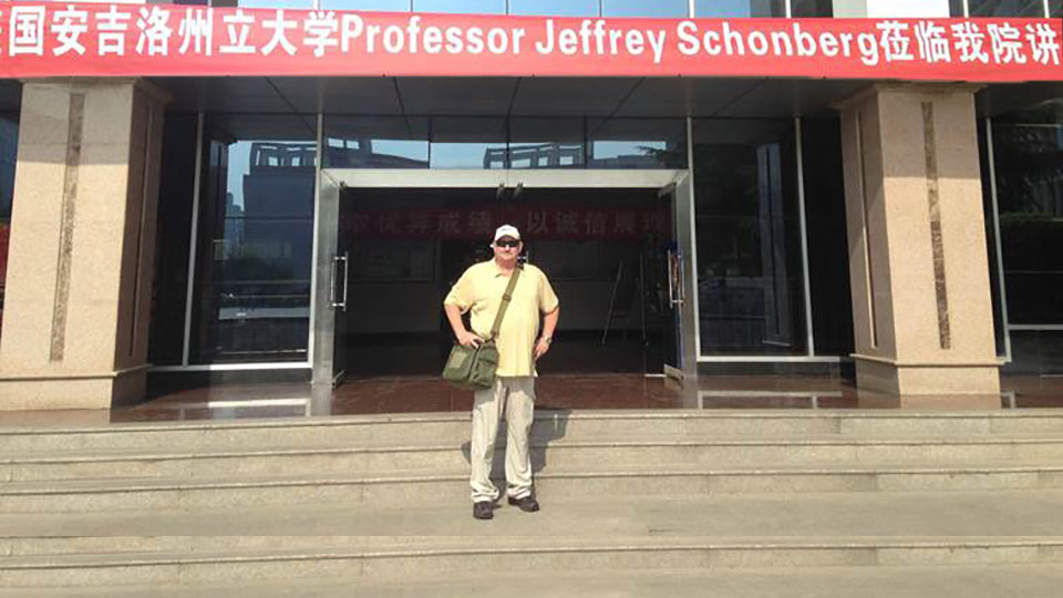 Dr. Schonberg and a welcome banner for him in China