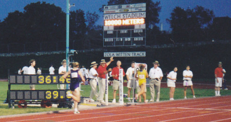 Cindy (in yellow) crosses the finish line to claim All-America status at the 1999 NCAA D-II National Championships in Emporia, Kan.