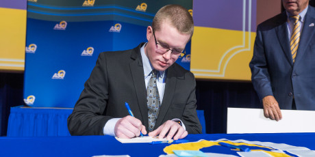 Logan Drake signs his Carr Scholarship to attend ASU in 2018.
