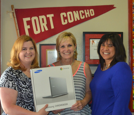 Dr. Lesley Casarez (left) and Dr. Kim Livengood (right) present a new computer to Lori Barton, principal of Fort Concho Elementary.