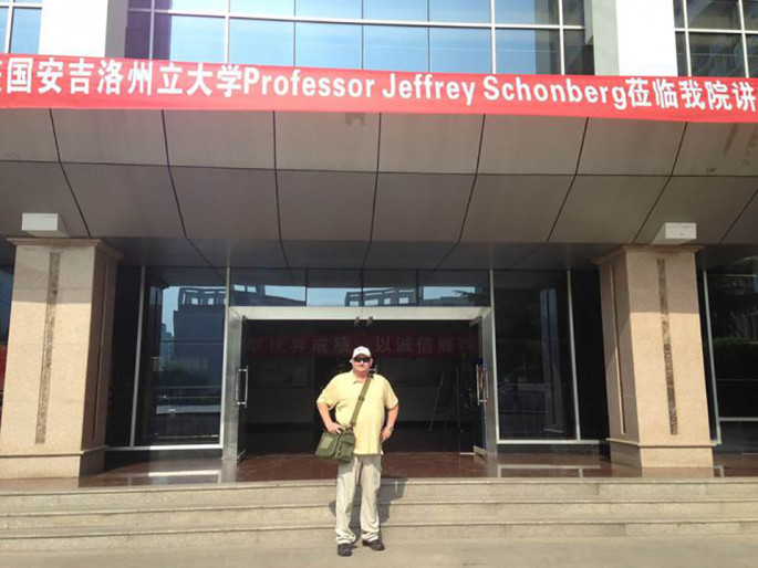 Dr. Jeff Schonberg under his official welcome banner on the steps of Xianyang Normal University in Xianyang, China