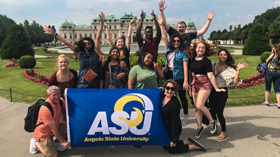 Students studying abroad and taking a photo with the ASU flag.