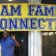 Parents holding Ram Hands in front of Ram Family Connection Sign.