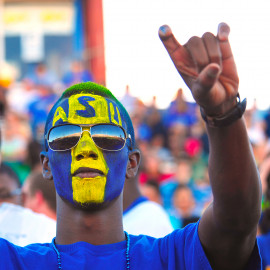 Spirited fan showing the rams head hand sign