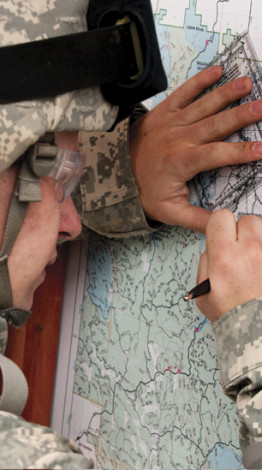 U.S. Army Spc. David McKelvey plots points on a map for a land navigation exercise at Spearfi...