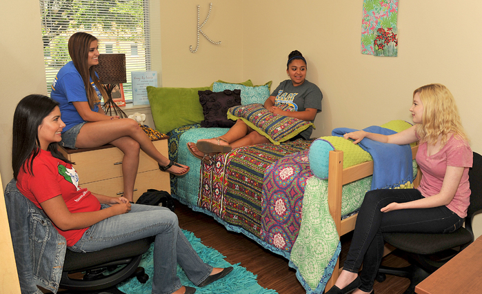 A group of Angelo State students relax in an on-campus dorm room.