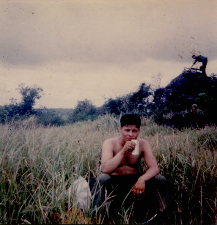 Guadalupe Carrasco pausing for a beverage while his friend sets up a machine gun position in the background in Vietnam (ci...