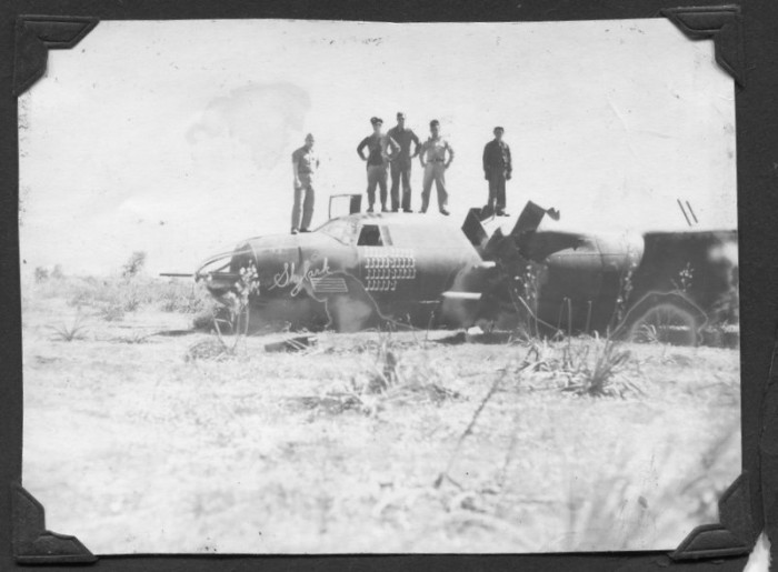 "Photo of men standing on the Skylark they had ""bellied in."""