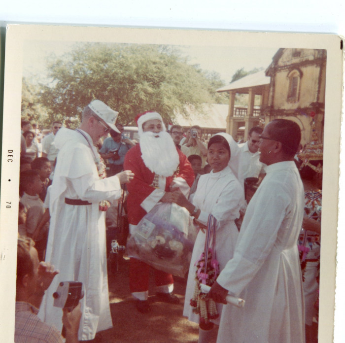 "Picture of Christmas celebration. Caption on the back reads, ""Father Martin (our base Cathol..."