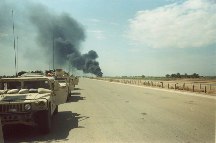 Photo taken from a procession of military vehicles. In the distance is a plume of smoke.