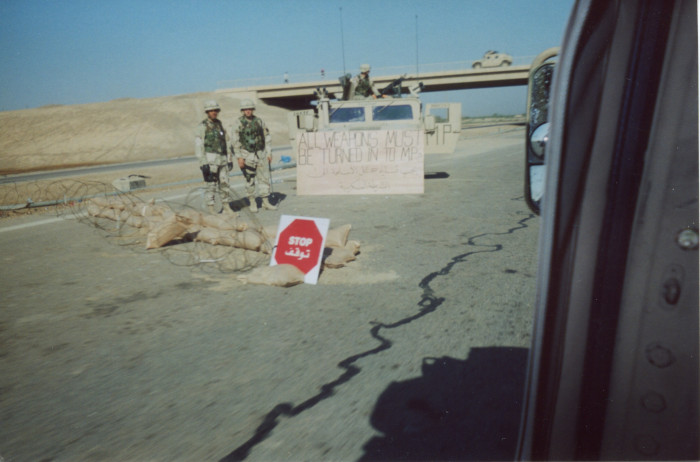 "Photo of a road stop. Sign in the photo reads, ""All weapons must be turned into MPs"""