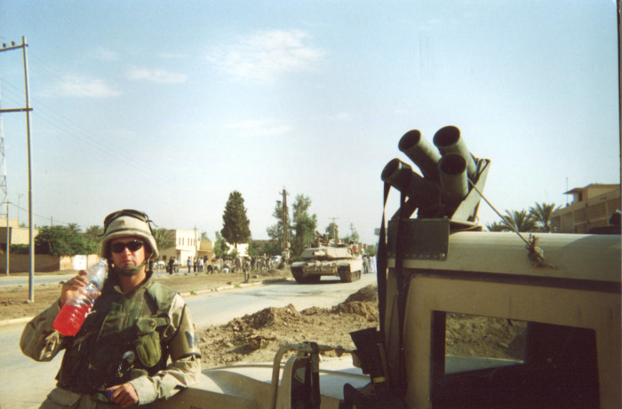 Photo of soldier drinking what looks like Gatorade while leaning on a Humvee. In the background is a crowd standing near a...