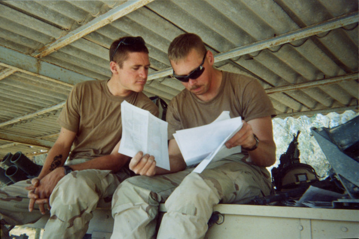 Photo of two soldiers looking over papers