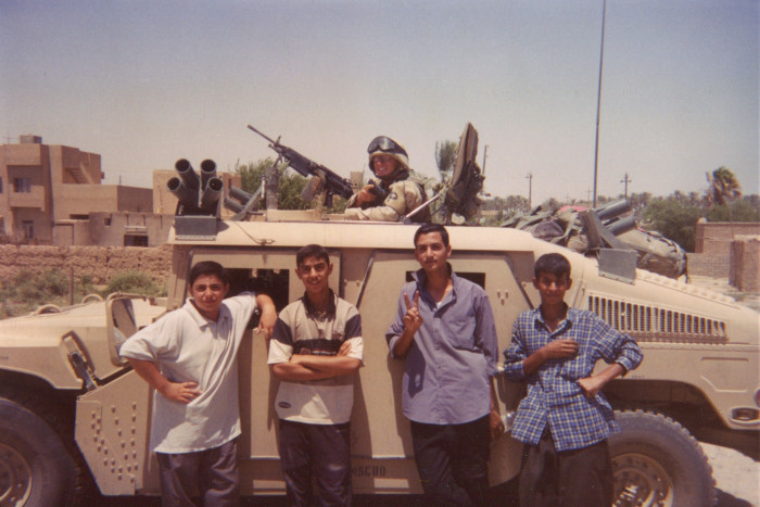 Photo of soldier and four Iraqi boys. The soldier is posed in the Humvee with the boys posed along the side.