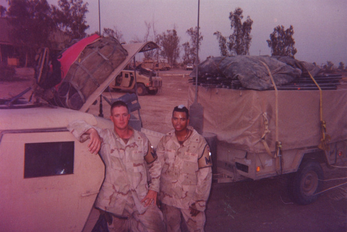 Photo of two soldiers standing in front of a Humvee