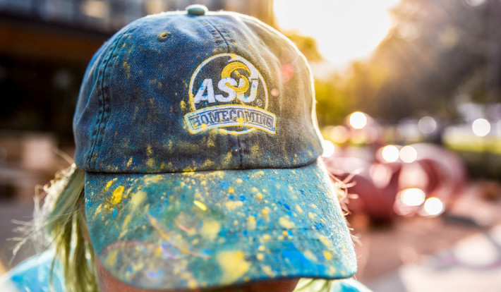 Homecoming baseball cap with blue and yellow paint on the brim.