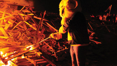 "Homecoming Tradition: Roscoe D. Ram helps light the Homecoming Bonfire, a longstanding tradition at Angelo State University. Symbolically, Roscoe is demonstrating the school motto, ""Fiat Lux,"" Latin for ""Let there be light."""