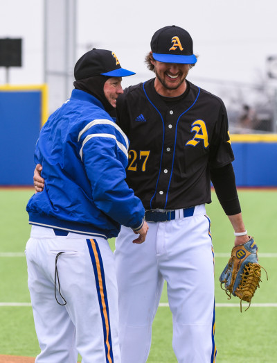 Kevin Brooks, head baseball coach, shares a laugh with Hauser.