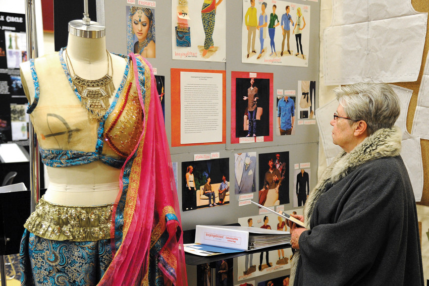 "ASU costumer Eldra Sanford took time during the theatre festival in February to look over ASU student Brittani Beggs' entry in costuming, saying, ""That young lady is exceptional. She did all of the beadwork on the costume. She did good research."""