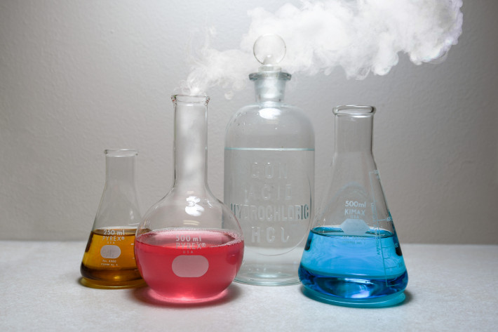 4 beakers with different liquids and smoke coming out of one of them