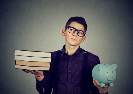 Student loan concept. Young man with stack pile of books and piggy bank full of debt rethinking f...