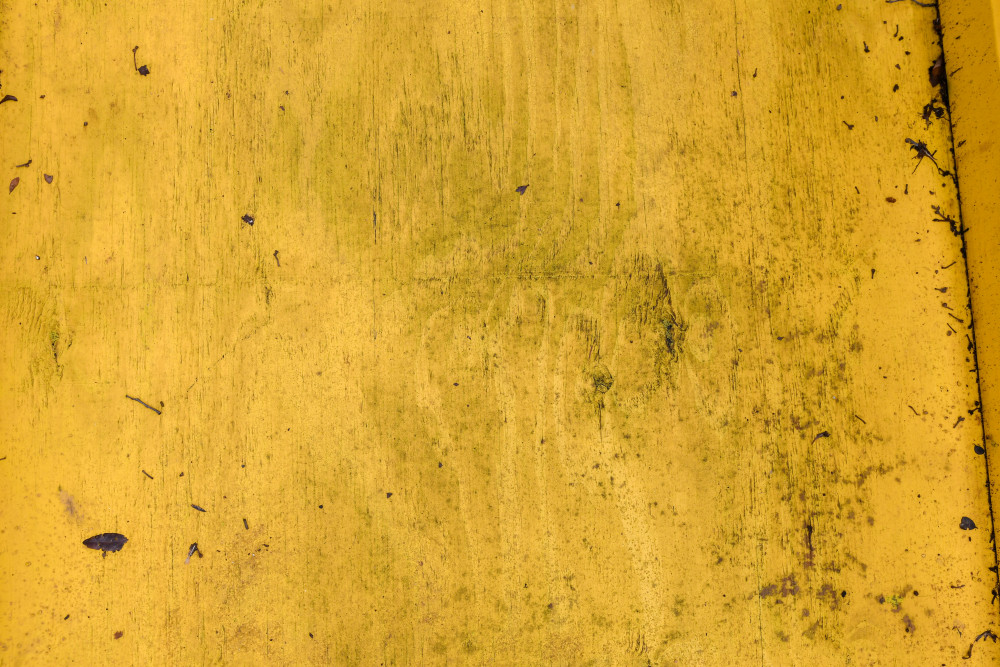 Close up photo of yellow painted wood