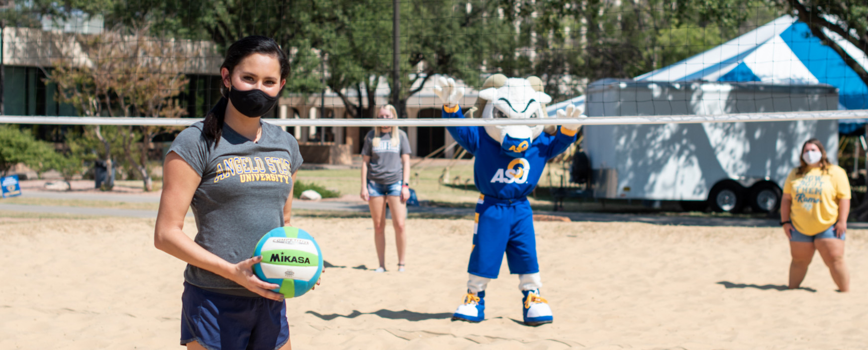 student playing sand volleyball with mascot