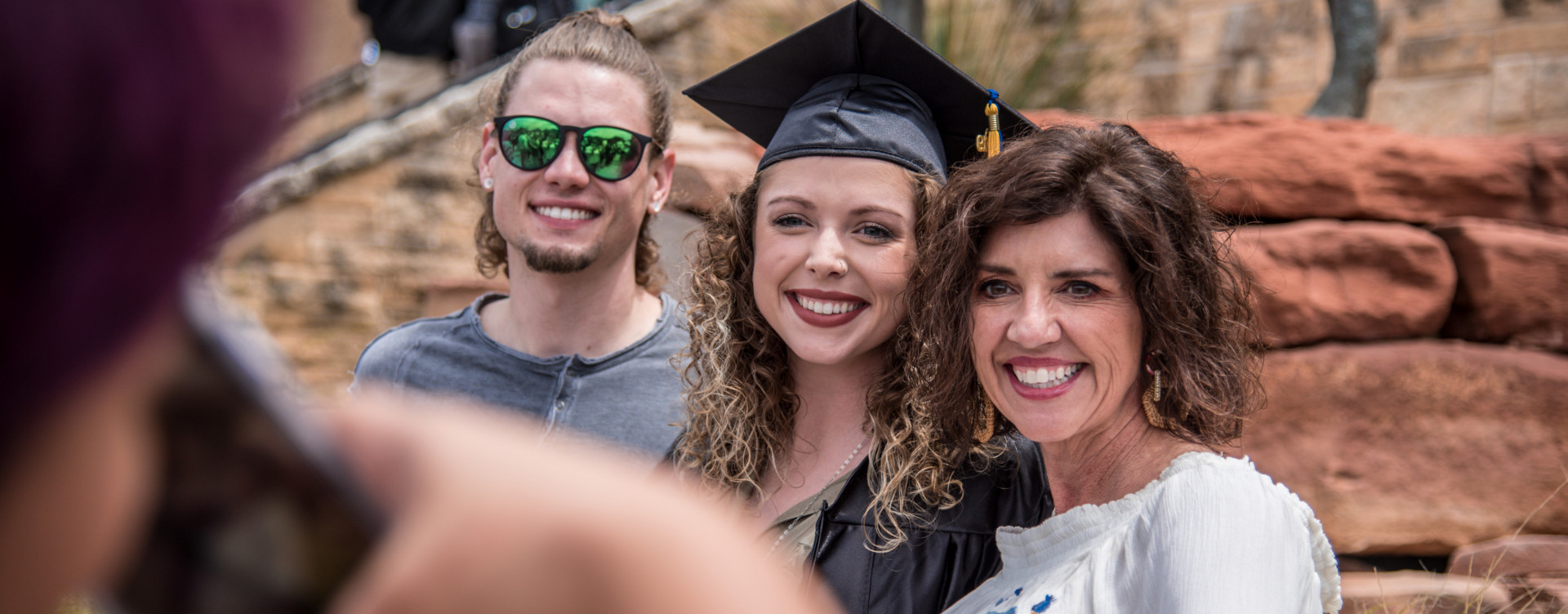 Family gathers after graduation ceremony.