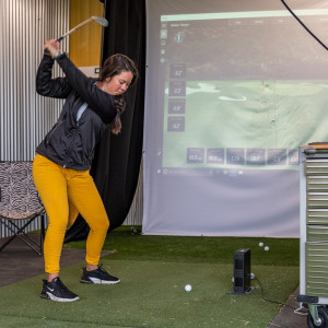 Student swinging golf club in golf simulator lab
