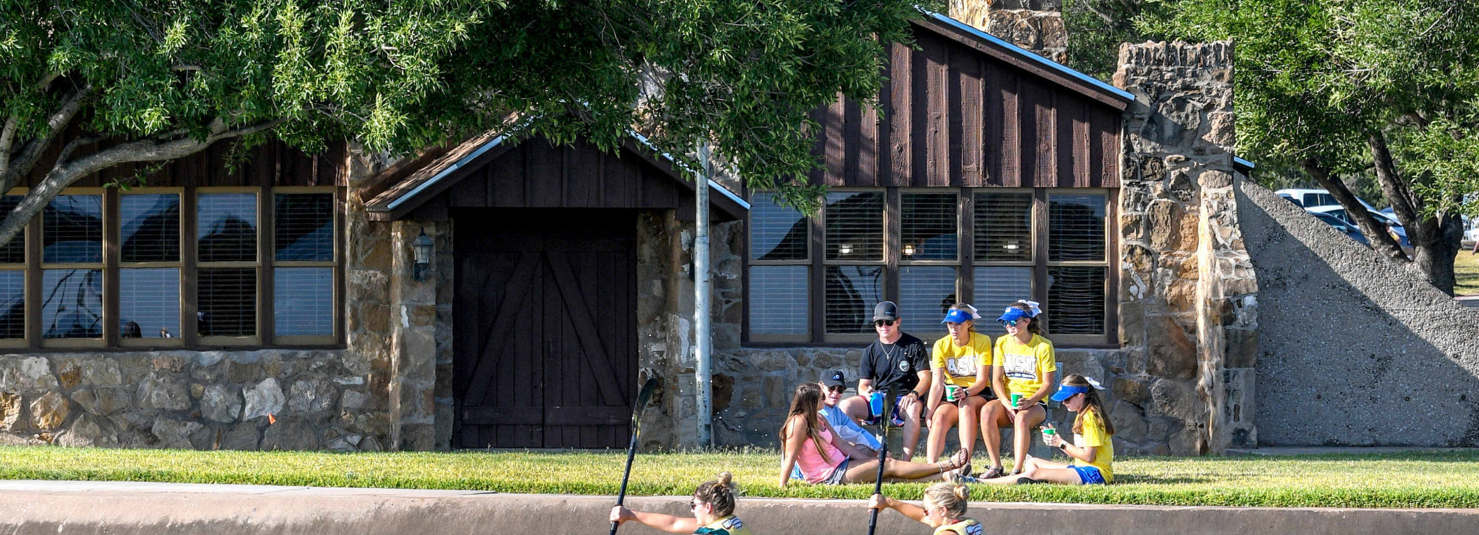 Students sitting outside the lake house