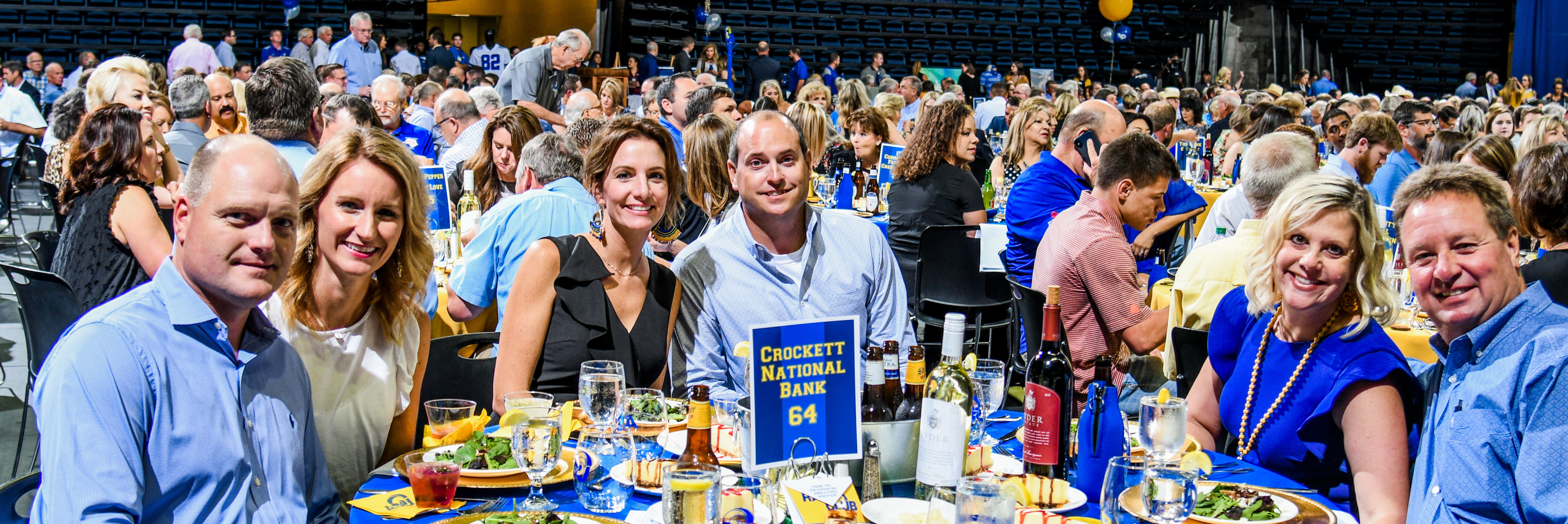 Member of Crocket National Bank sitting at table at Blue and Gold Auction