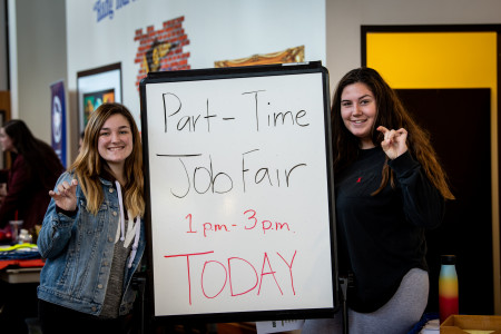 Students posing with part-time job fair sign