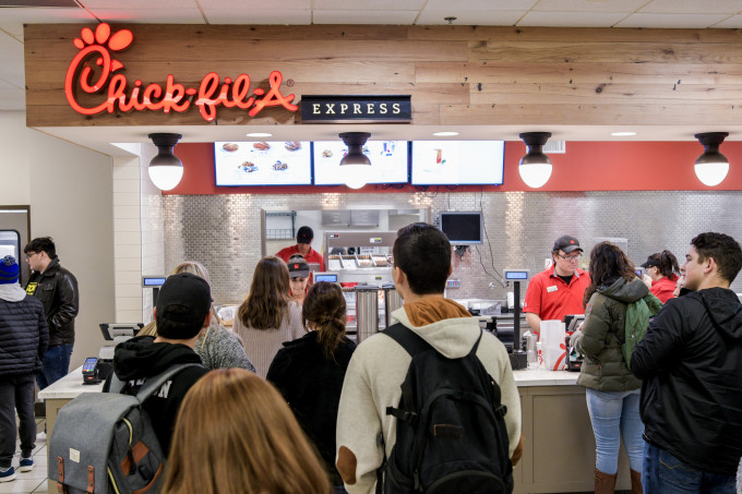 students waiting in line at Chic Fil A counter