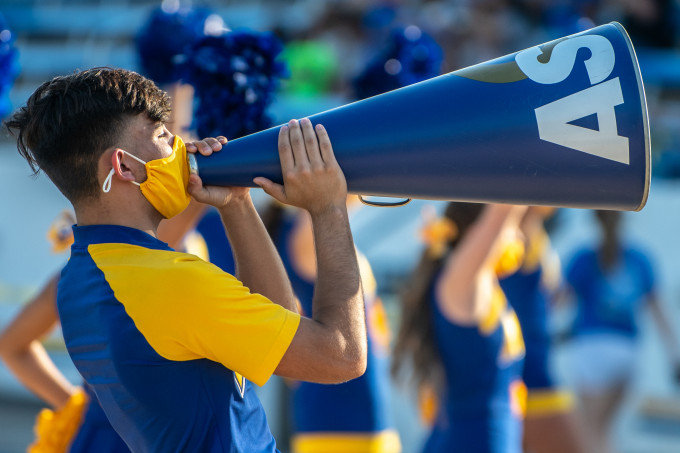 Male cheerleader yelling into a megaphone