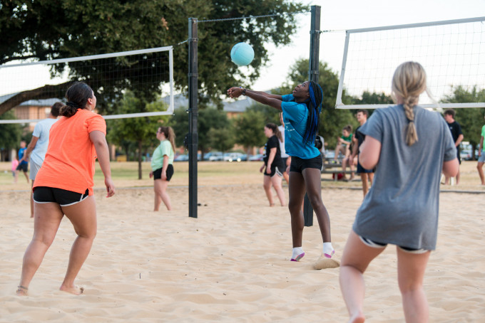 Students playing sand volleyball