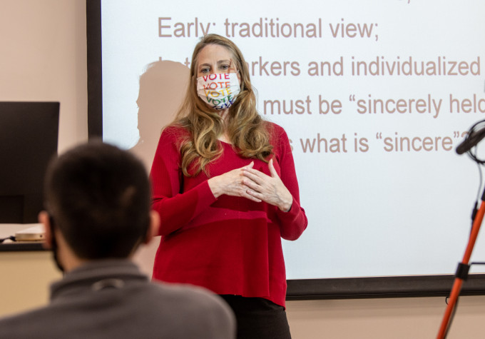 instructor wearing vote mask lecturing with projected screen behind her
