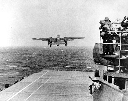 An Army Air Force B-25B bomber takes off from USS Hornet (CV-8) at the start of the raid, 18 April 1942. Note men watching from the signal lamp platform at right.
