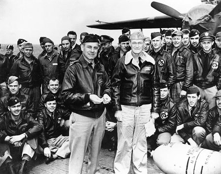 Lieutenant Colonel James H. Doolittle (left front), leader of the attacking force, and Captain Marc A. Mitscher, Commanding Officer of USS Hornet (CV-8), pose with a 500-pound bomb and USAAF aircrew members during ceremonies on Hornet's flight deck, while the raid task force was en route to the launching point.