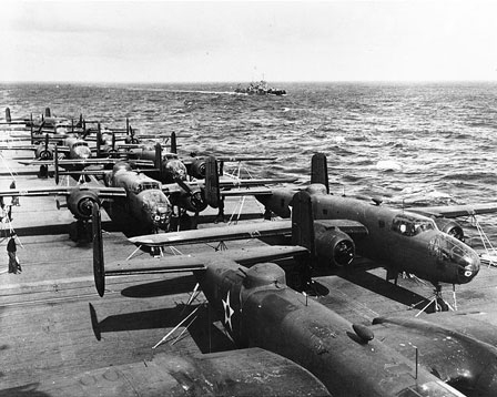View looking aft from the island of USS Hornet (CV-8), while en route to the mission's launching point. USS Nashville (CL-43) is in the distance. Eight of the mission's sixteen B-25B bombers are visible on the carrier's flight deck. Aircraft at right is tail # 40-2250, which was mission plane # 10, piloted by 2nd Lieutenant Richard O. Joyce, which attacked targets in the Tokyo area.