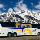 Bus in front of a snow covered mountain.