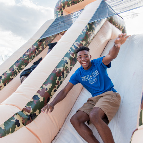 Student smiling jumping down a giant slide